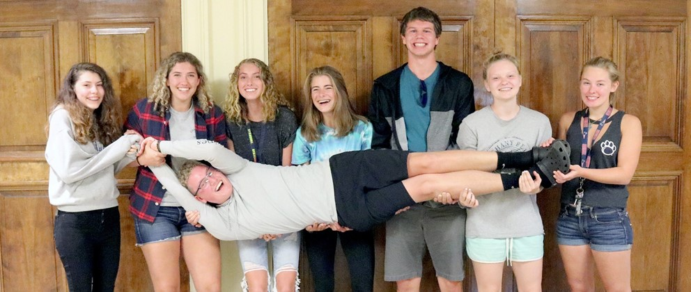High school senior boys and girls holding boy stretched horizontally